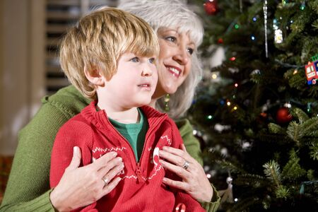 Four year old boy sitting on grandmothers lap by Christmas tree photo