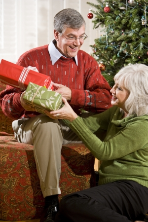 Happy senior couple exchanging Christmas gifts at home by tree photo