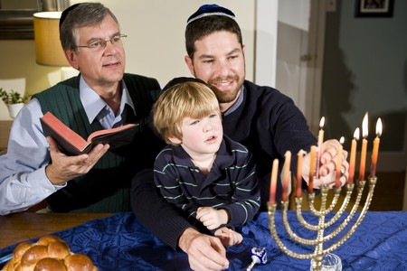 Four year old boy with grandfather and father lighting Hanukkah menorah photo
