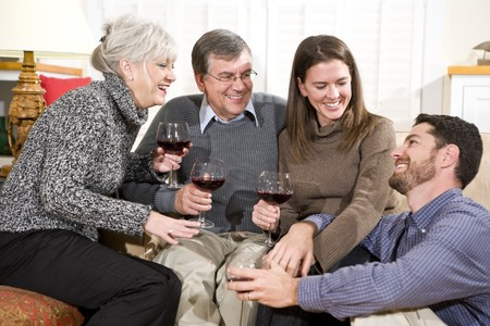 Mid-adult and senior couples enjoying conversation and wine photo