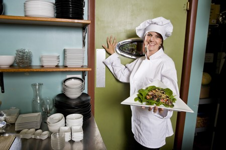 Chef working in restaurant standing at kitchen doorway with gourmet salad place photo