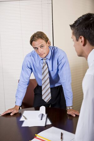 business skeptical: Business meeting - skeptical office worker looking at colleague in boardroom
