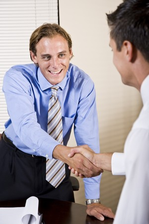 Two businessmen meeting in office shaking hands photo