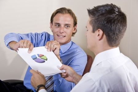 Businessmen discussing financial results looking at pie chart photo