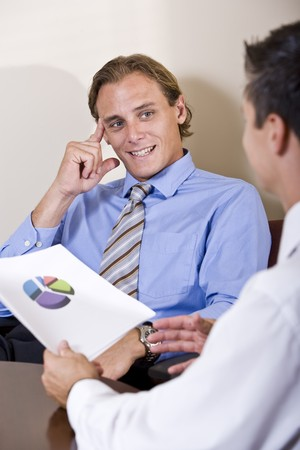 Businessmen discussing financial results looking at pie chart Imagens