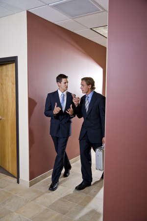 Two businessmen talking and walking down office corridor photo