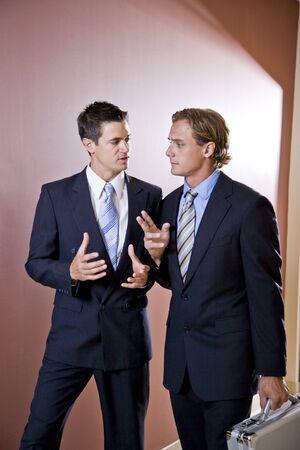 2 人のビジネスマンと話して、オフィスの廊下を歩いて