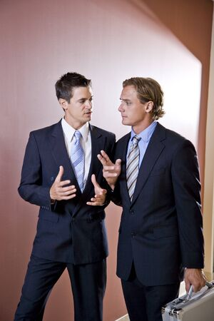 Two businessmen talking and walking down office corridor Banco de Imagens