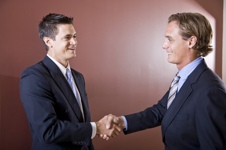 Businessmen wearing suits shaking hands photo