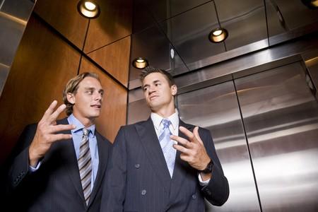 会話エレベーターに乗るビジネスマン