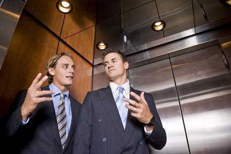 talk to the hand: Businessmen riding in elevator conversing Stock Photo