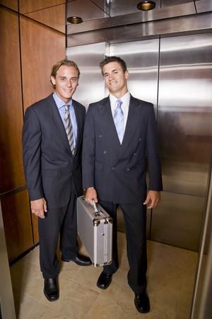 Businessmen standing in elevator photo