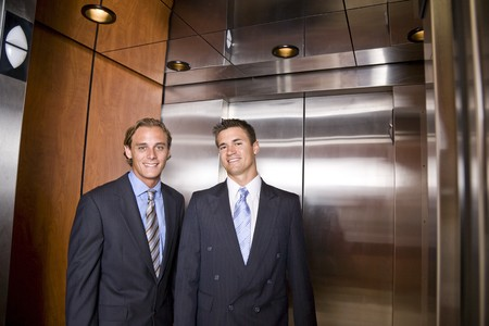 Businessmen riding in elevator photo