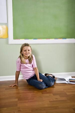 Back to school - girl in classroom by green blackboard, 8 years old photo