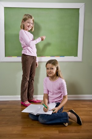 home schooling: Back to school - two 8 year old girls writing on blackboard doing homework