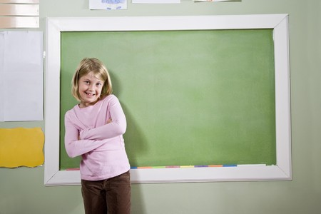 home schooling: Back to school - 8 year old girl smiling in classroom, standing by blackboard