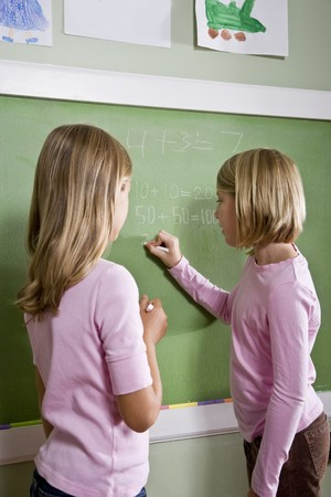 home schooling: Back to school - 8 year old girls writing on blackboard in classroom, doing math
