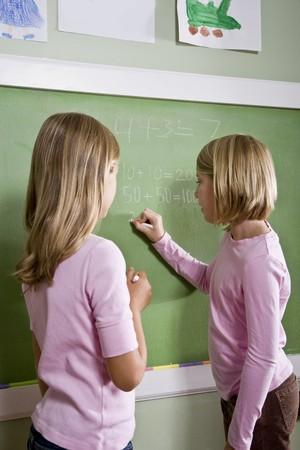 Back to school - 8 year old girls writing on blackboard in classroom, doing math