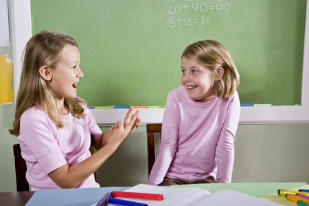 children talking: Back to school - 8 year old girls in classroom talking and smiling Stock Photo