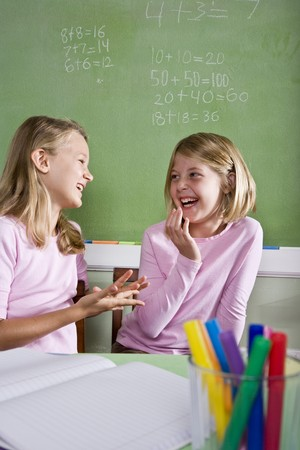 two friends talking: Back to school - 8 year old girls in classroom talking and smiling Stock Photo