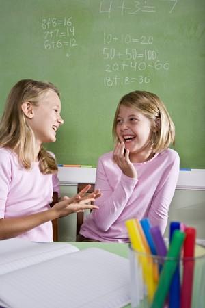dos personas conversando: Regreso a la escuela - 8 a�os de edad de las ni�as en aula hablando y sonriente