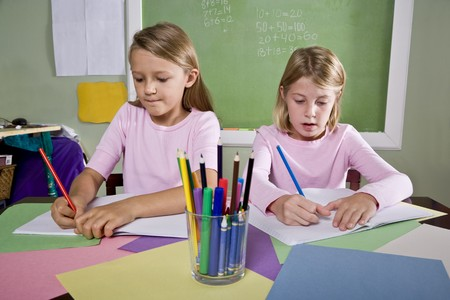 home schooling: Back to school - 8 year old school girls in classroom writing in notebook Stock Photo