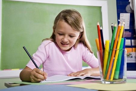 home schooling: Back to school - close-up of 8 year old girl writing in notebook in classroom