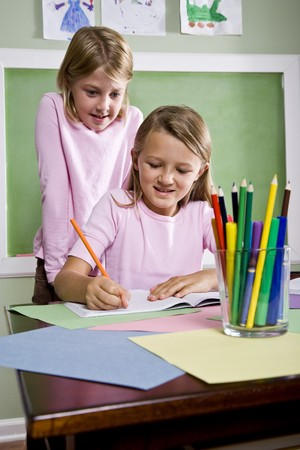 home schooling: Back to school - 8 year old girls writing in notebook in classroom Stock Photo