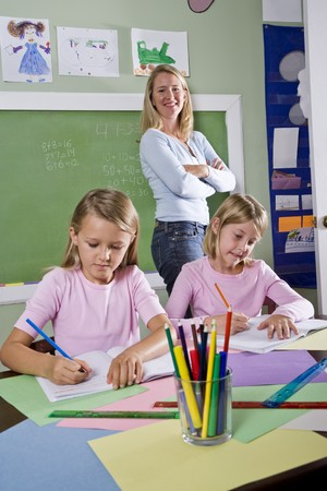 teacher with students: Back to school - 8 year old girls writing in notebooks in classroom with teacher watching Stock Photo