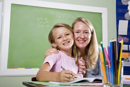 Back to school - 8 year old student and teacher writing in classroom Stock Photo