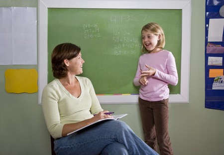 Back to school - 8 year old student and teacher talking by blackboard in classroom