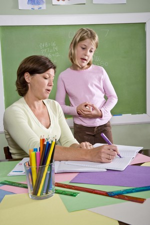 Back to school - teacher teaching 8 year old student in classroom Stock Photo - 7826672