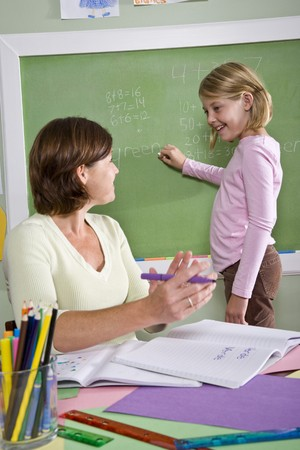 Back to school - 8 year old student and teacher by blackboard in classroom photo