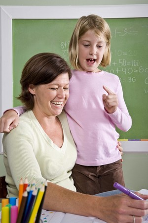 Back to school - teacher teaching 8 year old student in classroom photo