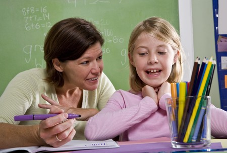 home schooling: Back to school - teacher teaching 8 year old student in classroom
