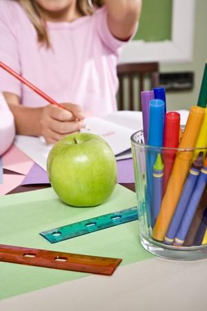 school desk: Apple for the teacher on student desk in classroom