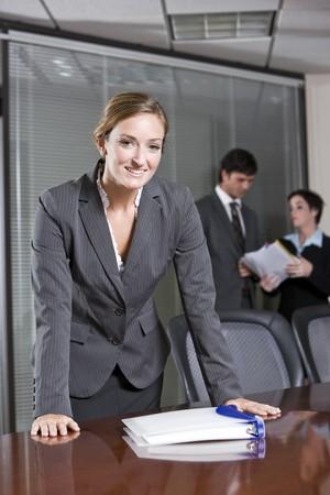 自信を持ってビジネスで女性の地位会議室、同僚のバック グラウンドでの会議