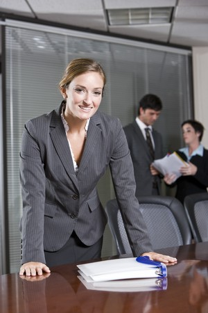 Confident business woman standing in boardroom, colleagues meeting in background 스톡 콘텐츠