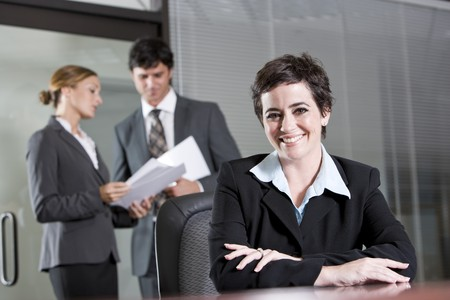 Businesswoman sitting in boardroom, co-workers discussing paperwork in background Stock Photo