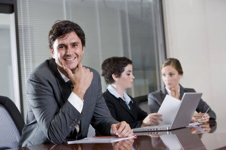 Businessman sitting in boardroom, female co-workers working in background photo