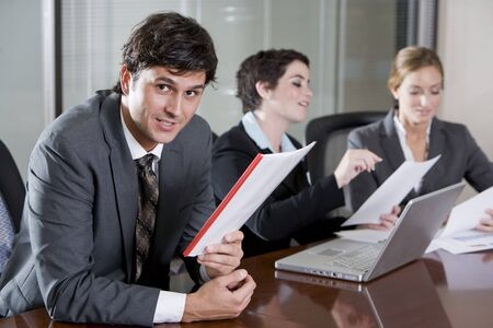 Businessman sitting in boardroom, female co-workers working in background Stock Photo - 7826748
