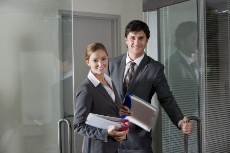 abriendo puerta: Dos trabajadores de oficina en trajes de apertura de la puerta de la sala de juntas