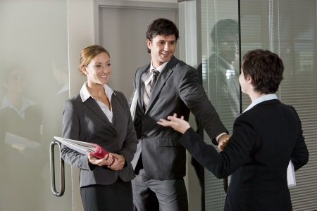 Three office workers chatting at open door of boardroom
