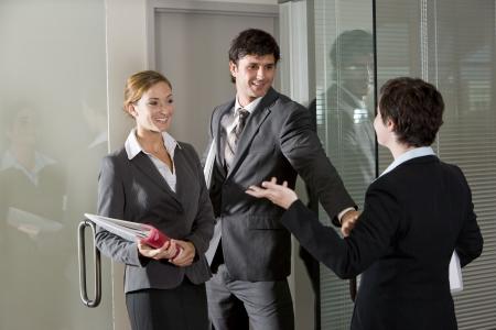 abrir puerta: Tres trabajadores de oficina chateando en abrir la puerta de la sala de juntas  Foto de archivo