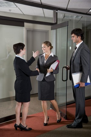 Three office workers shaking hands at door of boardroom Stock Photo