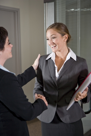 Two female office workers shaking hands at door of boardroom Stock Photo
