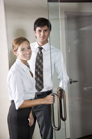 Two business people at door of office boardroom photo