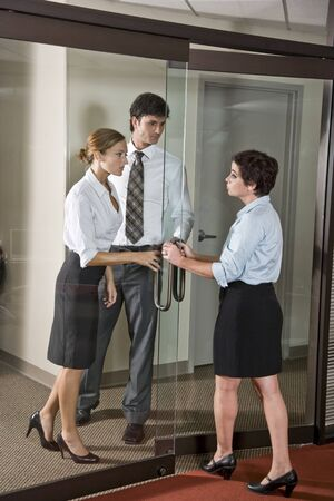Three office workers at door of boardroom, one inside, two outside photo