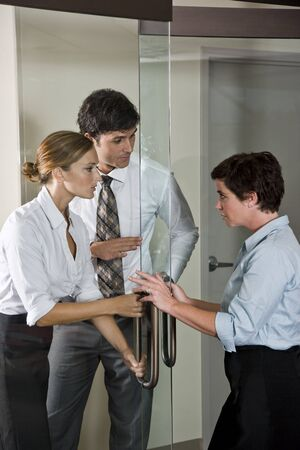 Three office workers at glass door of boardroom, one inside, two outside photo