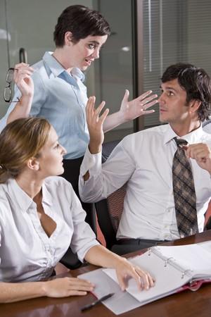 desacuerdo: Tres trabajadores de oficina en la sala de juntas, habiendo animada discusión